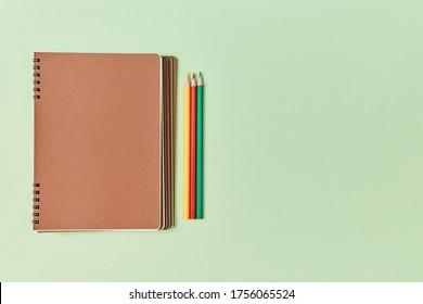 Bienvenue à l'école. Nouvelle année universitaire. Des tablettes avec espace de copie sur le capot et des crayons colorés. Concept de papeterie
