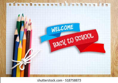 Welcome Back to School on squared white paper with colored pencils background