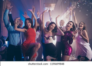 Welcome to the best night party! Leisure, lifestyle, careless, carefree concept. Luxury, style, cool look, trend ladies in fancy dress dance in city night club with good great mood raised hands up