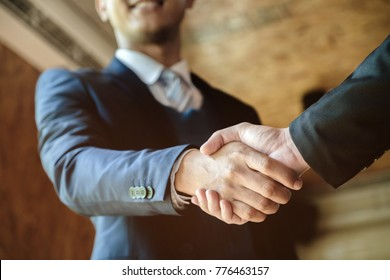 Welcome to board! Asian business people shaking hands with new partner meeting time after agree join new start up project, business co-working teamwork concept