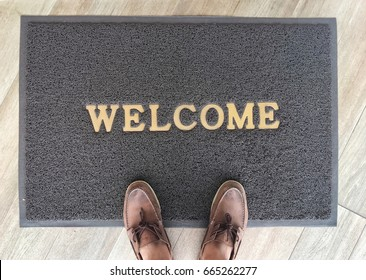 Welcome carpet gray color with shoe on it.