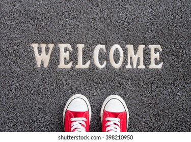 Welcome carpet with red sneakers on it.