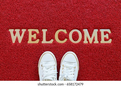 Welcome carpet with white sneakers on it.