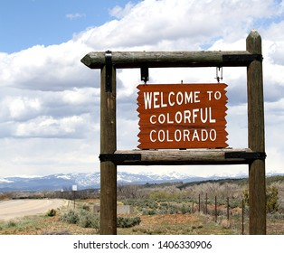 Welcome to Colorful Colorado sign located at the New Mexico border.  The sign is on wood posts and has a desert scene in the background with partly cloudy skies.