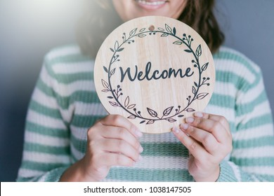 WELCOME CONCEPT.Women holding welcome word wooden board at home.