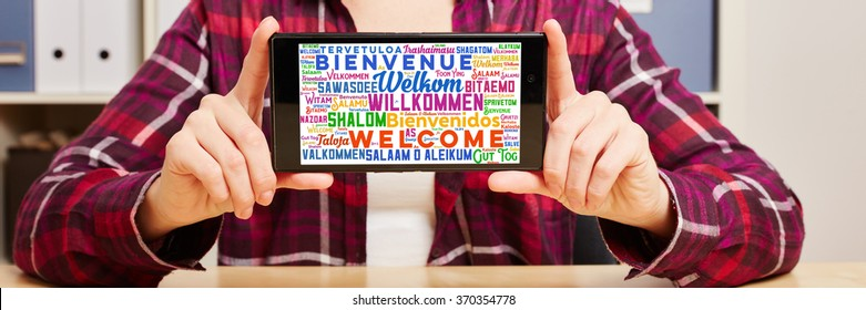 Welcome in different languages on a smartphone on the hands of a woman