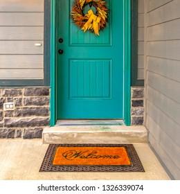 Welcome doormat in front of a door with wreath