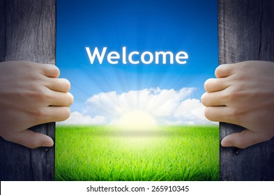 Welcome. Hands opening a wooden door then found a texts floating among new world as green grass field, Blue sky and the Sunrise.