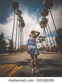 Welcome to Hollywood. Girl comes to Los Angeles for first time. Palm trees and greeting hat.