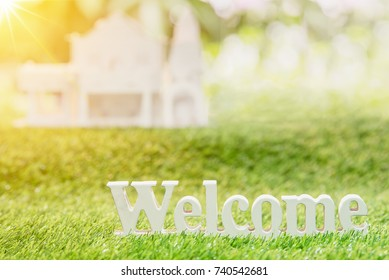 Welcome home on green grass background,paper family concept.
