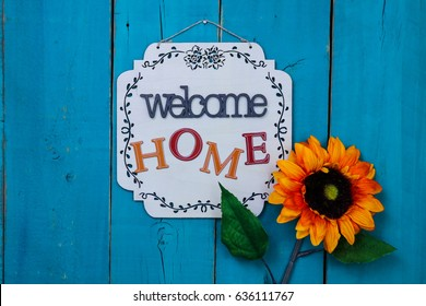 Welcome HOME sign with orange, yellow and red flower hanging on antique rustic teal blue wood door; Mothers Day, family, Memorial Day holiday background with painted copy space