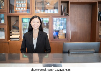 Welcome to the hotel,Happy young Asian woman hotel receptionist worker smiling standing at a Modern luxury  reception counter waiting for guests getting key card in hotel inn motel, lodge, hostel,