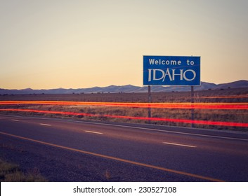 welcome idaho sign with light painting of passing vehicles with retro instagram filter at sunset or sunrise