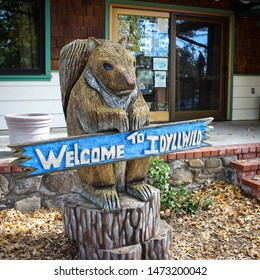 Welcome to Idyllwild sign being held by a wooden squirrel sculpture in California