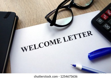 Welcome letter, pen, glasses and calculator on desk