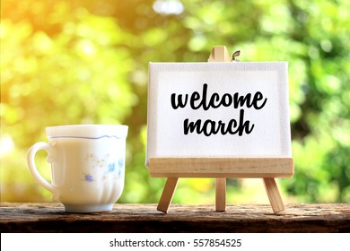 Welcome March. concept of coffee cup with stand board on morning background