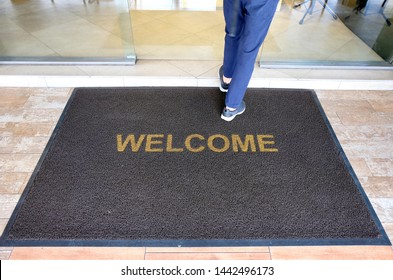 A welcome mat at the entrance of a cafe restaurant as a customer is seen entering through the front door.