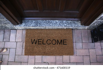 Welcome mat on a brick flooring by front door