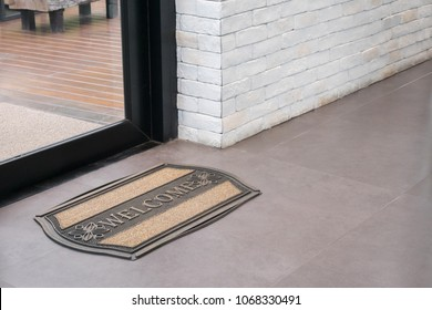 welcome mat on grey tiles in front of glass door with black aluminum frame