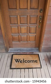 Welcome mat on a wooden deck by front door