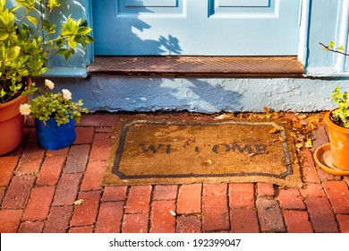 Welcome mat outside a cottage front door.