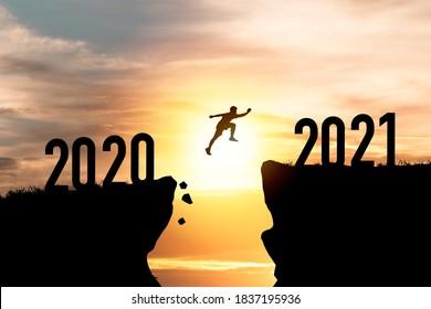 Willkommen frohe Weihnachten und glückliches neues Jahr im Jahr 2021,Silhouette Man springt von 2020 Klippe auf 2021 Klippe mit Wolkenschein und Sonnenlicht.