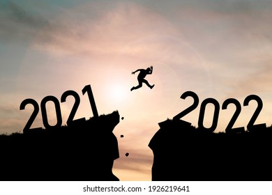 Welcome merry Christmas and happy new year in 2022,Silhouette Man jumping from 2021cliff to 2022 cliff with cloud sky and sunlight.