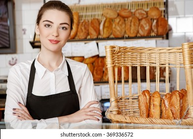 Welcome to my shop! Shot of a beautiful female baker posing in the bakery store