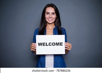 "Welcome at new home. Beautiful modern smiling woman in a jeans shirt is holding a sign with the inscription ""welcome"" on a gray background isolated."