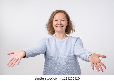 Welcome or Nice to meet you concept. European woman in blue sweater with stretched hands handshake. She wants to hug her firends. Expression emotion and feelings concept.