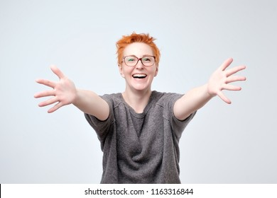 Welcome or Nice to meet you concept. European woman in gray sweater and glasses with stretched hands handshake. She wants to hug her firends. Expression emotion and feelings concept.