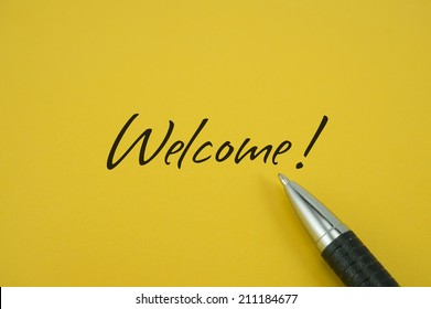 Welcome! note with pen on yellow background