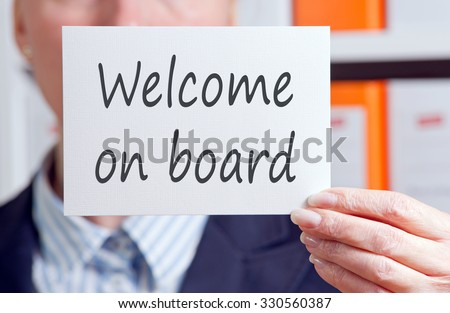 Welcome on board - Businesswoman holding white sign with text in the office