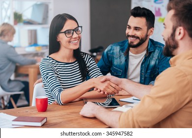 Welcome on board! Confident young woman and man shaking hands and smiling while sitting at the desk in office