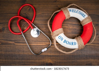 WELCOME ON BOARD. Lifebuoy with text and doctor's stethoscope on wooden background
