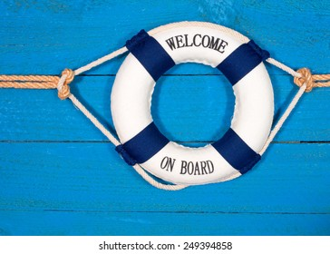 Welcome on Board - Lifebuoy with text on blue wooden background