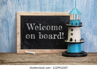Welcome on board, phrase written on vintage chalkboard with lighthouse on rustic wooden background