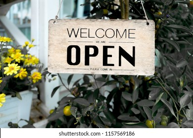 Welcome Open sign hanging by rope on rustic antique wood door on tree background