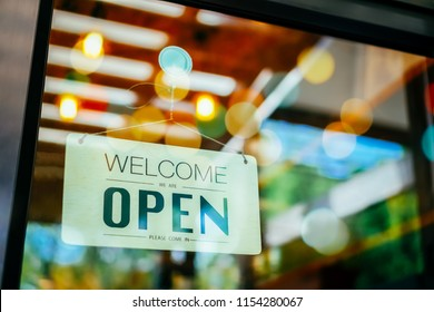 Welcome open sign on door of coffee cafe shop.