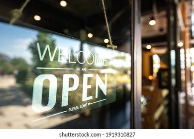 """""""Welcome, open"""" signboard of the cafe and food restaurant which is display at the entry. The signboard is behind the glass window, cause the lighting reflection from outside environment."""