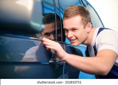 Welcome to our car service station. Closeup image of a smiling handsome car mechanic wiping the car in specialized service station