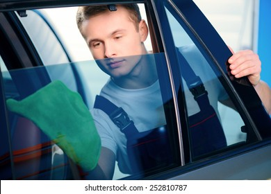 Welcome to our car service station. Closeup image of a handsome car mechanic wiping the car windows with tinting foil and smiling at camera in specialized service station