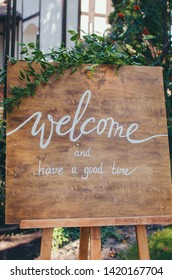 Welcome to our celebration. Handwritten calligraphy text sign board on wooden panel in the garden with tree twig