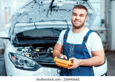 Welcome to our service station. Portrait of a smiling handsome mechanic in uniform posing by the car at car service station holding electronic repair tools