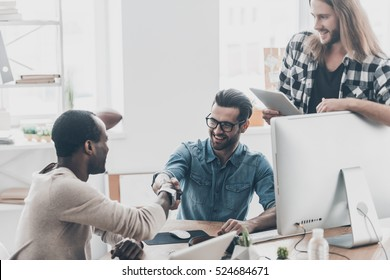 Welcome to our team! Three businesspeople having a meeting while two of them shaking hands and smiling