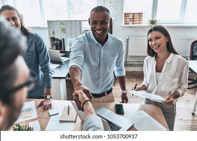Welcome to our team! Top view of young modern men in smart casual wear shaking hands and smiling while standing with their colleagues in the board room