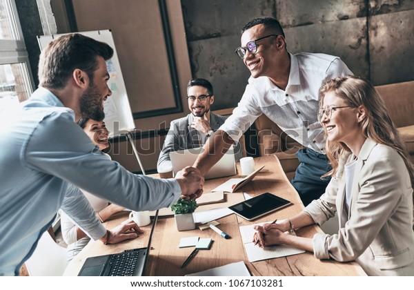 Willkommen bei unserem Team! Top-Sicht auf junge moderne Männer in intelligenter, lockerer Kleidung, die beim Arbeiten im Kreativbüro Hände schüttelt