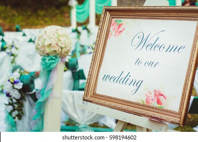 Welcome to our wedding table in golden frame on wedding ceremony in the garden