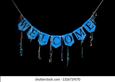 Welcome party banner. Blue bunting letters spelling the word welcome with celebration streamers isolated against black background. Black text written on card.