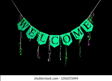 Welcome party banner. Green bunting letters spelling the word welcome with celebration streamers isolated against black background. Black text written on card.